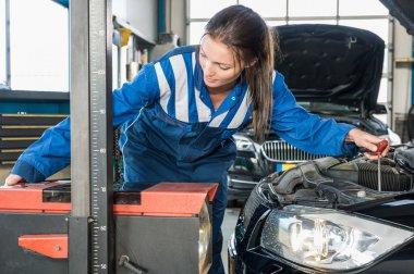 Female mechanic mounting car