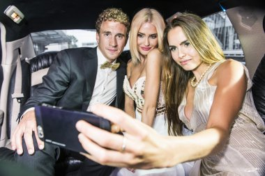 man with female friends taking selfie