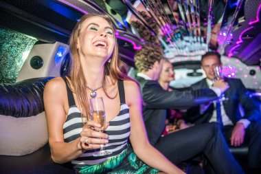 woman with champagne flute in limousine