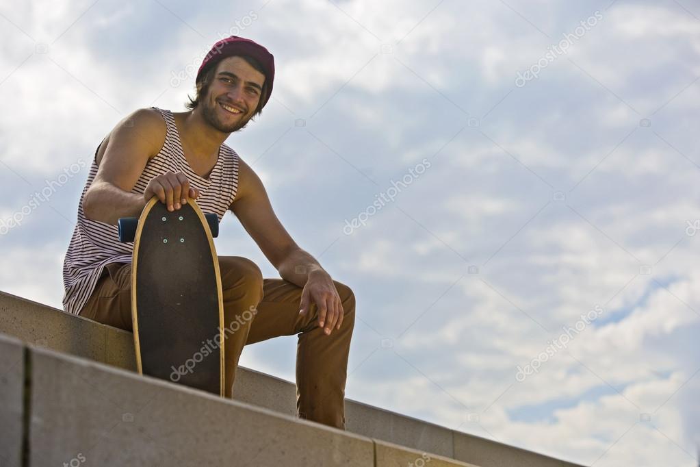 Smiling skateboarder sitting on concrete steps