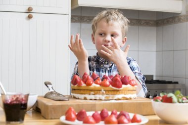 Boy licking fingers with batter
