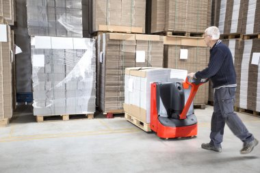 Worker Pushing Stock On Handtruck