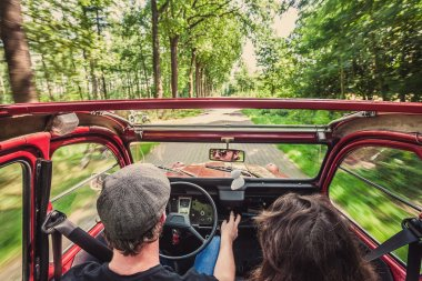 Couple in an ondtimer  driving