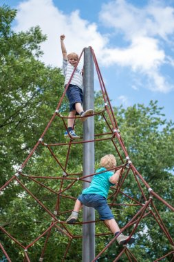 Two boys climbing a rope ladder