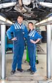 Two smiling mechanics  standing