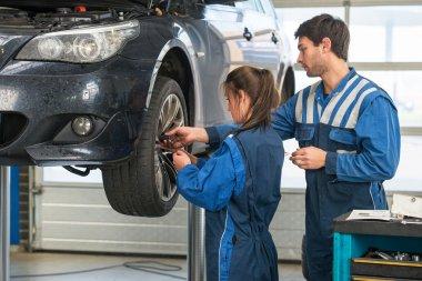 Mechanic teaching an intern