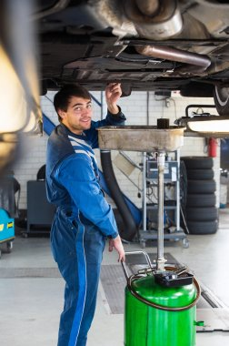 Mechanic checking vehicle oil