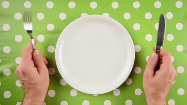 Pohled shora nervózní hladové mužské ruce u jídelního stolu