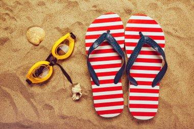 Pair of thongs or flip flops on beach sand