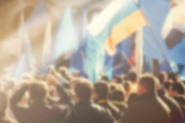 Blur unrecognizable crowd at political meeting, cheering audienc