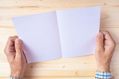 Man holding blank brochure as mock up copy space