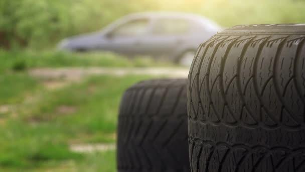 Detailní záběr pneumatiky s provozem v pozadí