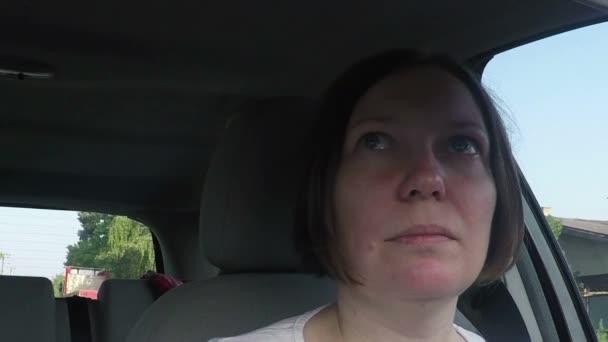 Žena v autě a při pohledu do zpětného zrcátka