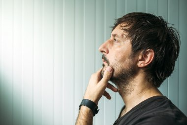 Pensive unshaven man with hand on chin making decision, judging or evaluating something, studio profile portrait with copy space stock vector
