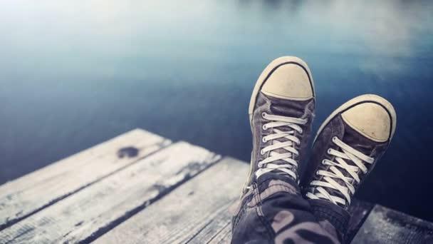 Mann mit gekreuzten Beinen entspannt sich auf Ufersteg