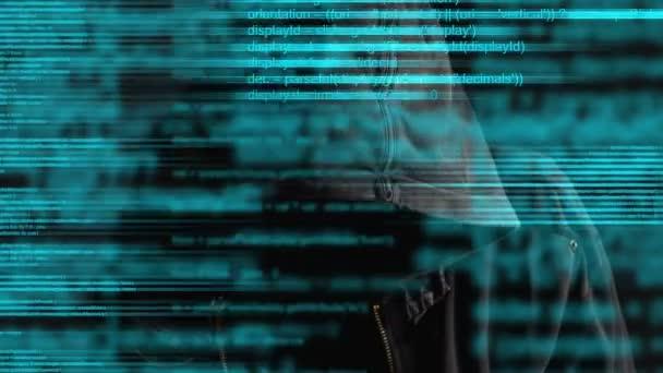 Anonymní kapucí anonymní počítačový hacker s programovací kód z monitoru
