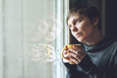 Sad alone Woman Drinking Coffee in Dark Room