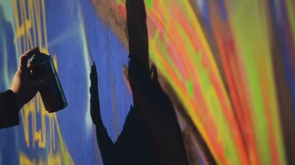 Graffiti művész festék permetezés a falon, a szabadban Street Art koncepció, Handheld 1920 x 1080 filmszerű tónusú Hd felvétel