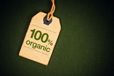 100 Percent Organic Food on Vintage Price Label Tag Label on Green Grunge Textured Backgroundas, Top View. stock vector