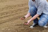 Coltivatore che controlla la qualità del terreno di fertili terreni agricoli Farm