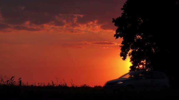 Siluety auta v večer, při západu slunce jízdy