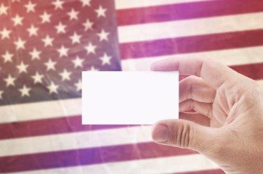 Man Holding Blank Business Card Against USA National Flag