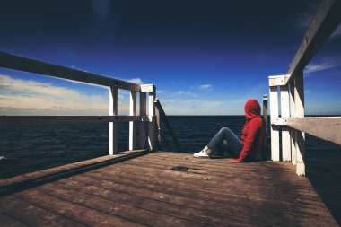 Alone Woman in Red Shirt at the Edge of Pier