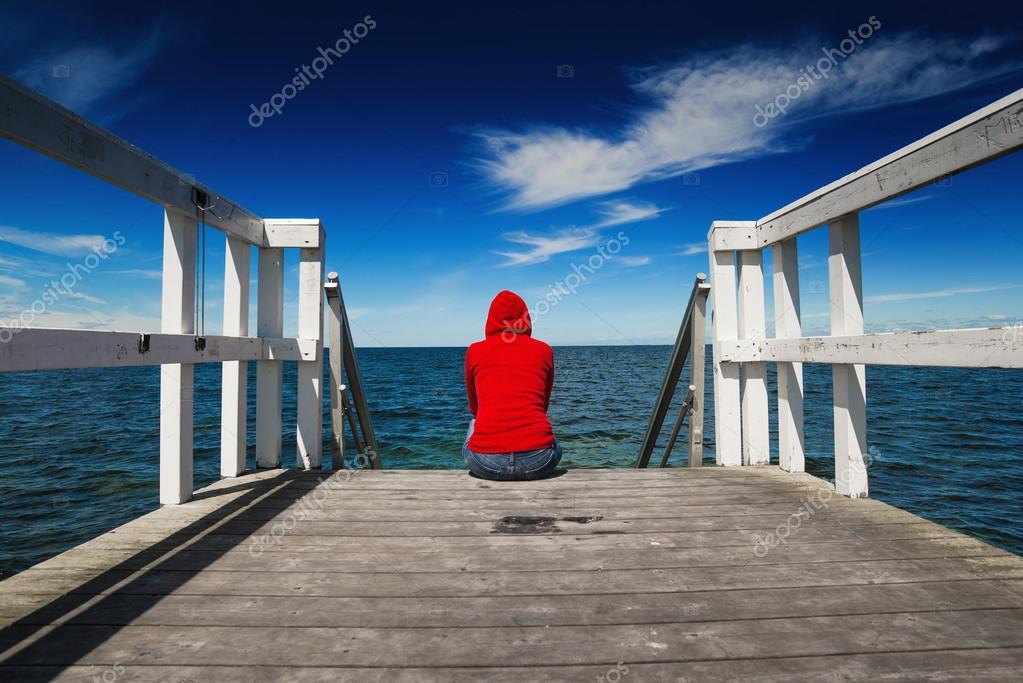 Alone Woman in Red Shirt at the Edge of Jetty