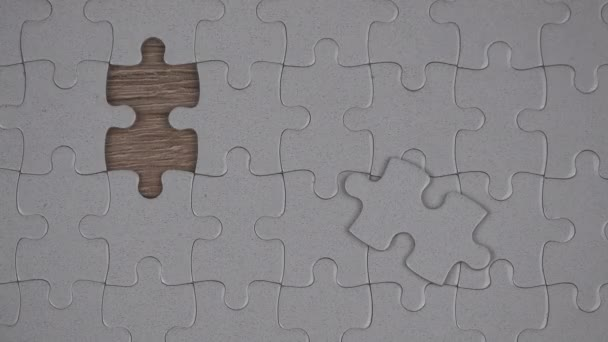 Male hand putting a missing piece into jigsaw puzzle