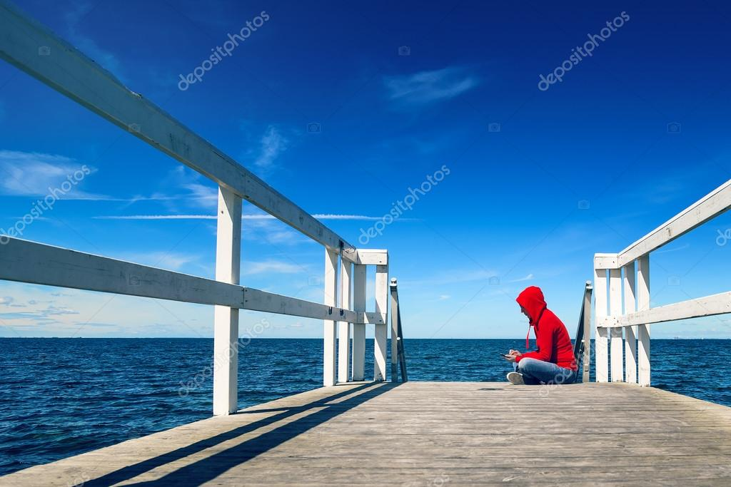 Woman Texting on Smart Phone at Ocean Pier