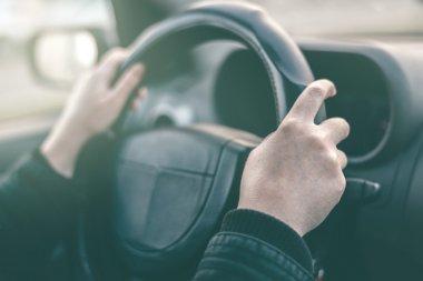 Female driver hands griping steering wheel