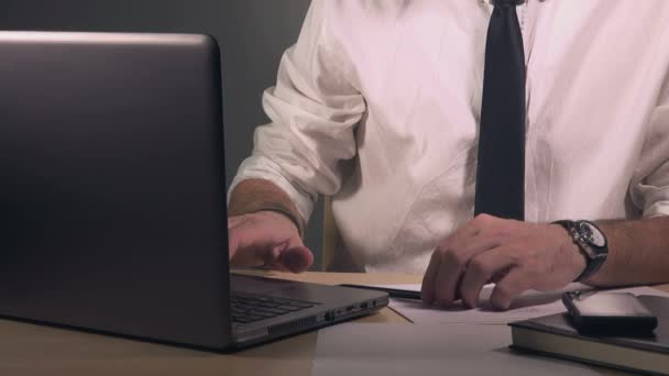 Freelance businessman writing notes and using laptop computer