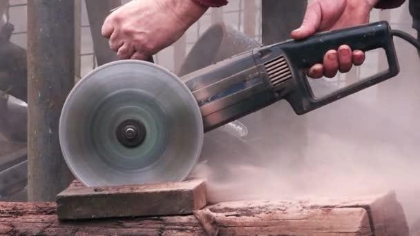 Daráló munkás vágja kő blokk elektromos kézi fűrésszel