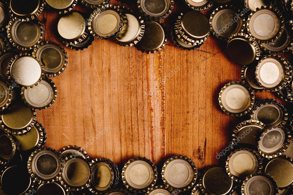 Beer bottle caps frame over wooden background — Stock Photo ...