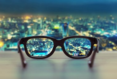 Night cityscape focused in glasses lenses. Vision concept stock vector