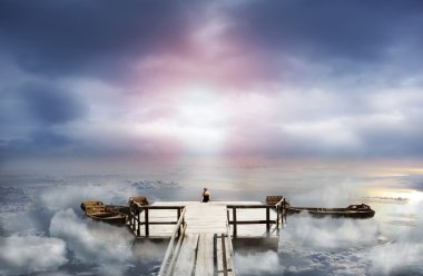 Woman sitting on an old pier