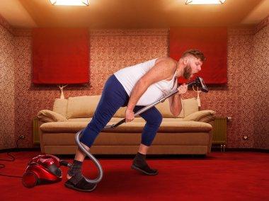 Adult man sings to the vacuum cleaner