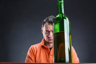 Addict man with bottle of wine