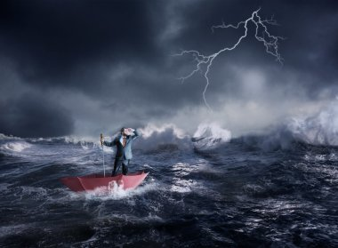 Businessman in umbrella sails in storm