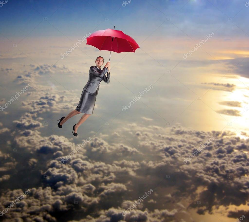 Dreamy woman flying in sky with umbrella