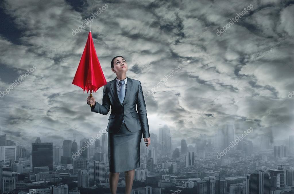 Businesswoman with closed umbrella