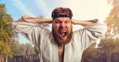 Aggressive karateka is tightening black belt