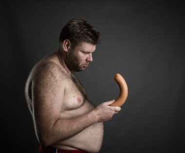 fat man looking at sausage