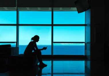 Silhouette of woman with cell phone