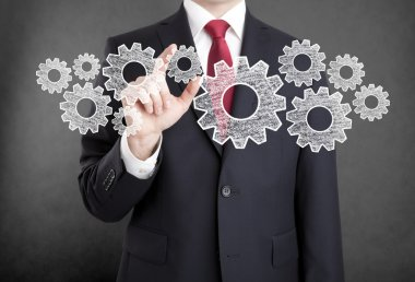 Businessman with gears, concept of well organized work process.