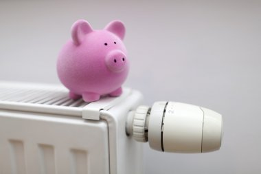 Pink piggy bank on radiator. Energy saving concept.