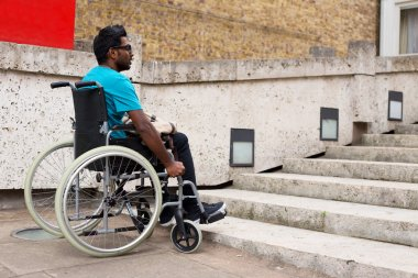 A young indian man in a wheelchair