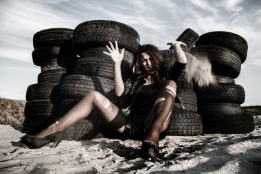 Woman at the background of an old tires