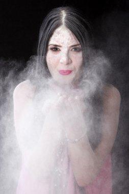 Portrait of a woman blowing a white powder