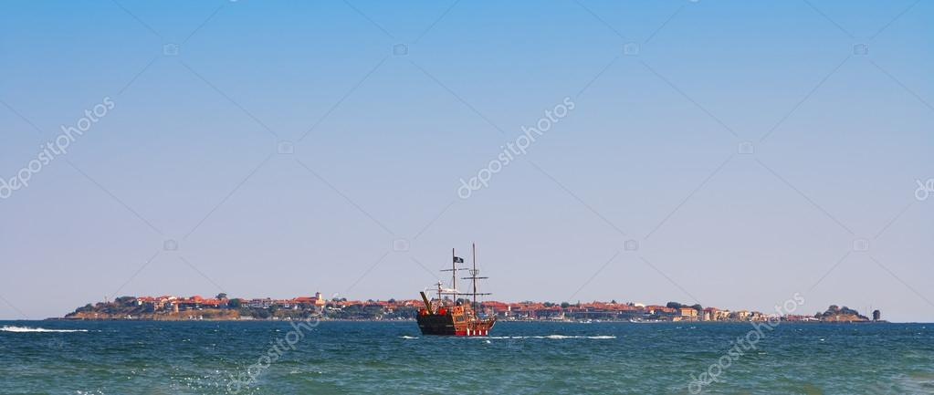 Historic old pirate ship in the ocean near island
